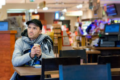 Man drinking coffee sitting in Cafe. Focus is on face. Royalty Free Stock Image