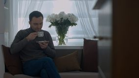 Man drinking a coffee on sofa and looking through window at home. Professional shot in 4K resolution. 071. You can use it e.g. in your commercial video stock photos