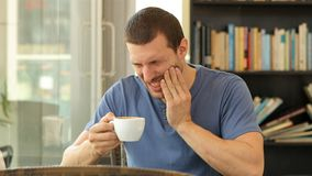 Man drinking coffee and suffering tooth ache. Sitting in a restaurant stock footage