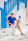 Man drinking coffee to go in traditional greek village outdoors. Young boy with hot coffee in outdoor cafe in Mykonos Royalty Free Stock Photography