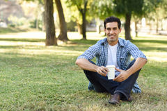 Man drinking coffee to go in an urban park Stock Images