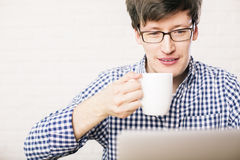 Man drinking coffee and using laptop. Closeup of young man using laptop and drinking coffee on blurry brick wall background Royalty Free Stock Photo