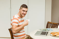 Man drinking coffee using laptop Stock Images