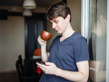 Man drinking coffee and using mobile smartphone Stock Images