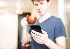 Man drinking coffee and using mobile smartphone Royalty Free Stock Photos