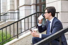 Man drinking coffee using phone Royalty Free Stock Photography