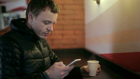 Man drinking coffee and using smartphone.  stock footage