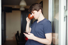 Man drinking coffee and using smartphone Royalty Free Stock Photos