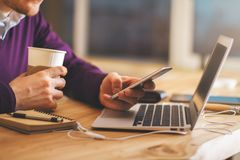 Man drinking coffee using smartphone. Side view and close up of unrecognizable businessman drinking coffee and using smartphone at blurry desk with laptop Royalty Free Stock Images