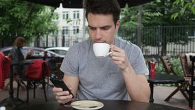 Man Drinking Coffee and using Smartphone while Sitting in Cafe Terrace stock photography