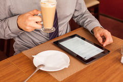 Man drinking coffee  and using tablet computer. Stock Photography