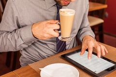 Man drinking coffee and using tablet and mobile Royalty Free Stock Photography