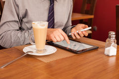 Man drinking coffee and using tablet and mobile Stock Photo