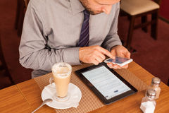 Man drinking coffee and using tablet and phone Stock Photography