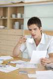 Man Drinking Coffee and Working on Finances Stock Photography