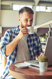 Man drinking coffee and working with laptop Stock Images