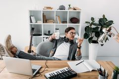 Man drinking coffee at workplace. Young relaxed musician drinking coffee at workplace and looking away Stock Photos