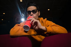 Man drinking cold drinks while watching movie Stock Photo