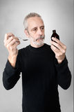 Man Drinking Cough Syrup. A mature man is pouring cough syrup in a spoon to cure his sore throat and bronchitis Stock Images