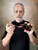 Man Drinking Cough Syrup. A mature man is pouring cough syrup in a spoon to cure his sore throat and bronchitis Stock Photography