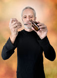 Man Drinking Cough Syrup. A mature man is pouring cough syrup in a spoon to cure his sore throat and bronchitis Stock Photo