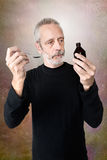 Man Drinking Cough Syrup. A mature man is pouring cough syrup in a spoon to cure his sore throat and bronchitis Stock Photos