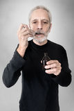 Man Drinking Cough Syrup. A mature man is drinking a spoon of  cough syrup to cure his sore throat and bronchitis Stock Image