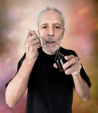 Man Drinking Cough Syrup. A mature man is drinking a spoon of  cough syrup to cure his sore throat and bronchitis Stock Photography