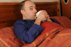 Man drinking from cup in bed Royalty Free Stock Photo