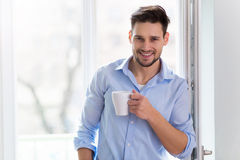 Man drinking cup of coffee near window Royalty Free Stock Images