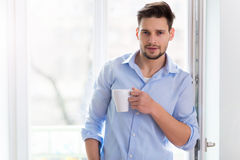 Man drinking cup of coffee near window Royalty Free Stock Photography
