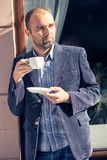Man drinking a cup of coffee. Picture of handsome man walking on the street and looking aside while holding cup of coffee Royalty Free Stock Image