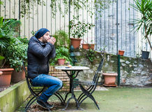 Man drinking from a cup in a garden Stock Image
