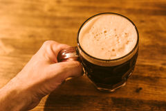 Man drinking dark beer in british dimpled glass pint mug Royalty Free Stock Images