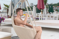 Man Drinking Glass of Beer on Oceanfront Patio Stock Photos