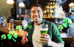 Man drinking green beer at bar or pub. People, leisure and st patricks day concept - happy young man drinking green beer at bar or pub Royalty Free Stock Photo