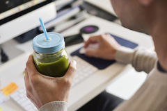 Man drinking a green smoothie at the office stock images