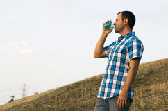 Man drinking on a hillside. Man standing on a hillside outside drinking from a cup wearing a plaid shirt Royalty Free Stock Photo