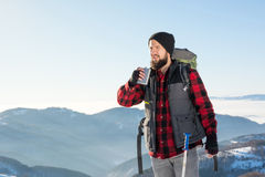 Man drinking from a hip flask on a hiking trip. Man drinking from a hip flask on winter hiking trip royalty free stock image