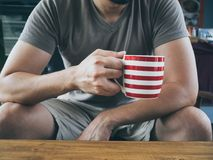 Man drinking hot coffee tea or cocoa. Stock Image
