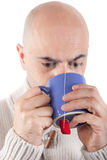 Man drinking a hot drink in a mug. Stock Image