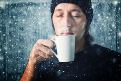 Man drinking hot tea. Man drinking tea from cup while the snow is falling Stock Photo