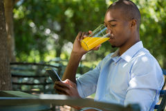 Man drinking juice while using mobile phone at restaurant Royalty Free Stock Image