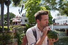 Man drinking juice from watermelon standing in Malacca. In hot summer day stock images