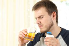 Man drinking a medicine with bad taste. Disgusted man drinking a medicine with bad taste at home Stock Images