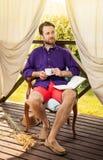 Man drinking morning coffee outdoor on garden terrace stock photography