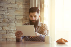 Man drinking morning coffee with tablet stock photos