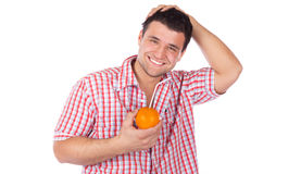 Man drinking orange juice Stock Photos