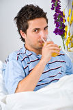 Man drinking orange juice in bed. Young man drinking a glass with orange juice in the morning and sitting on bed,see more in People home Stock Photography