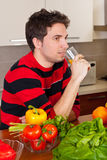 Man drinking orange juice in kitchen. With fresh vegetables on table Stock Photos